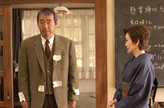 Imagen de la película en la que se puede ver al profesor, con sus notas colgando de su chaqueta, junto a su cuñada, que es la persona que contrata a la asistenta.