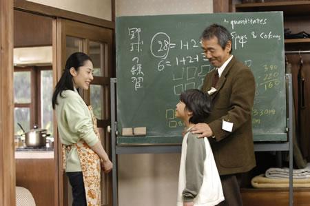 Imagen de la película en la que se puede ver a los tres personajes principales, el profesor, la asistenta y Root, con una pizarra al fondo con los números perfectos 6 y 28