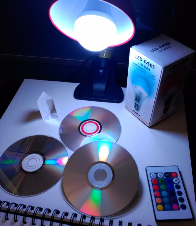 """El """"sistema experimental"""", la bombilla que cambia de color con su mando a distancia, un prisma y unos CDs."""