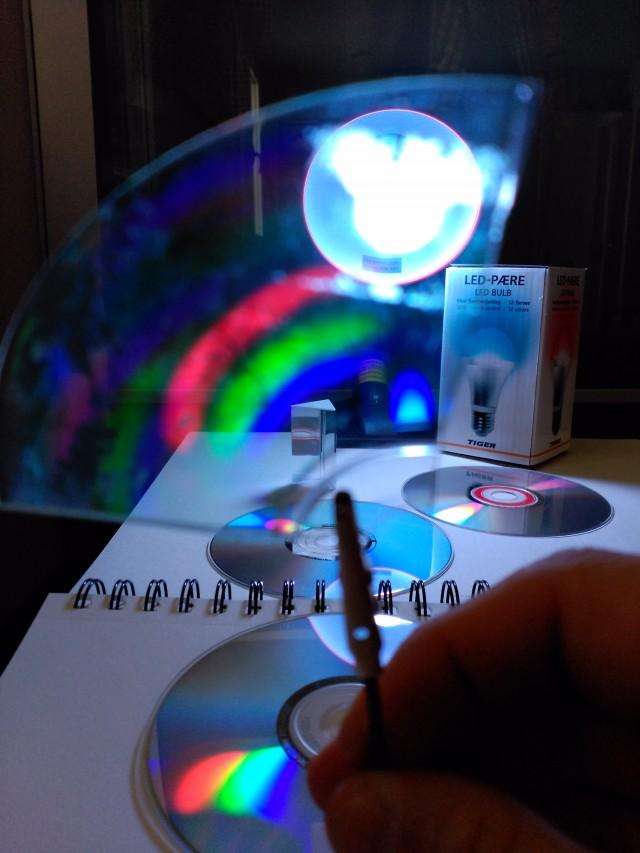 """Espectros de la luz de la bombilla (en posición """"blanco"""") tanto en reflexión (en el CD de abajo) como en transmisión (en el trozo de CD sujeto frente a la lámpara. En ambos casos se ven tres manchas de color separadas: azul, verde y rojo."""