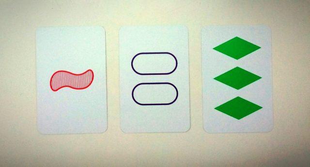 Tres cartas del juego SET con diferentes diseños utilizando las cuatro características mencionadas, forma, color, número y fondo