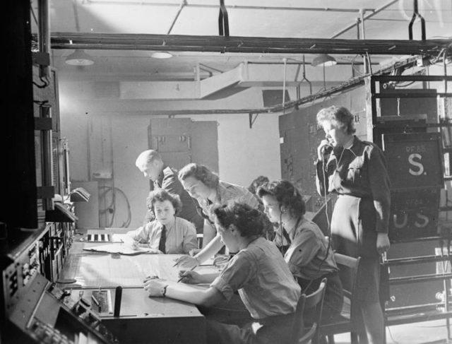 Sala de operaciones de radar de la base de la RAF en Bawdsay, Suffolk (Reino Unido) en algún momento de la Segunda Guerra Mundial. La operadora de radar es apenas visible al fondo a la derecha. El resto del equipo traslada a un mapa las informaciones que recibe via intercomunicador la persona que se comunica con la operadora. La comunicación con la unidad operativa de la base (cazabombarderos) la realiza la comandante de vuelo Wright, al teléfono, responsable de la sala.